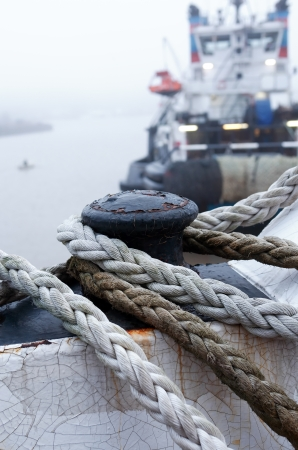 Shipboard with rope closeup on background with industrial ship on the river at morning photo