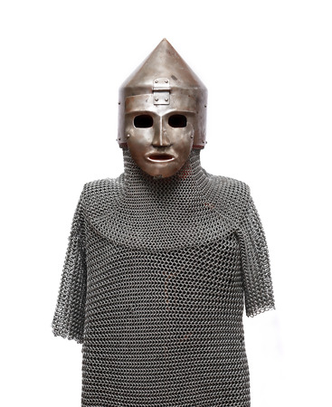 Mannequin clothed ancient helmet and chain armour on white background