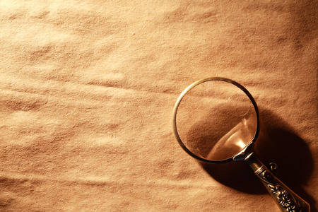 Vintage magnifying glass on nice old paper background