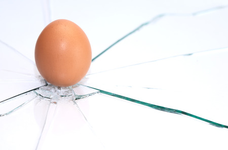 Brown chicken egg standing on shattered glass background photo