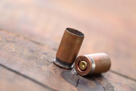 gun shell: Conchas de arma de la pistola sobre fondo de madera con el espacio libre