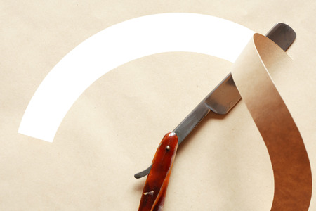 Straight razor on paper with blank hole for text. Clipping path is included photo