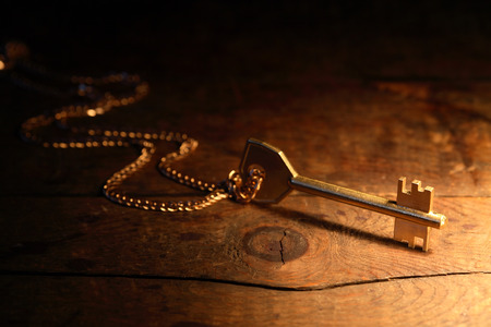 Key with chain on wooden background under beam of light photo
