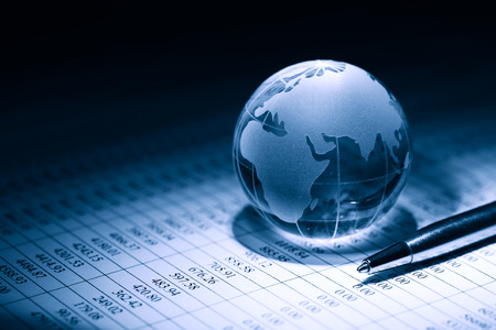 financial globe: Business concept. Glass globe near pen on background with table of numbers