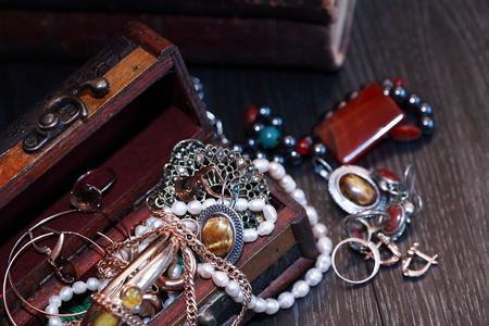 Nice vintage open box full of various jewelry on dark wooden background photo
