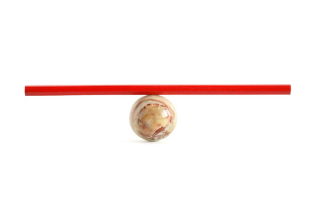 Red pencil on ball made from semiprecious stone on white background photo