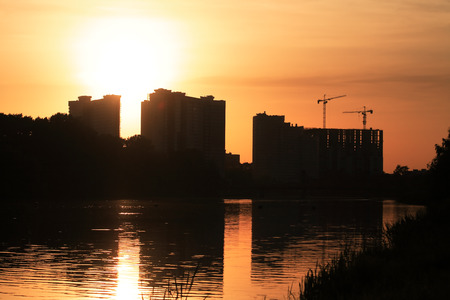 housebuilding: House-building with reflection in river against beautiful sunset