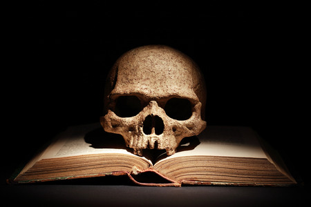 One human skull on old open book against dark background