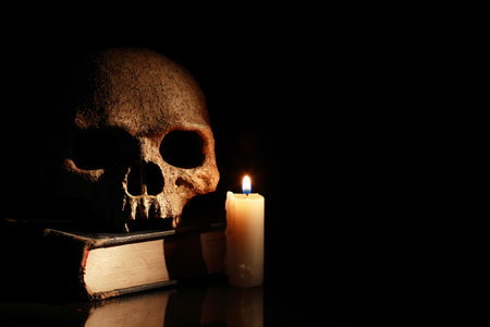 satanism: One human skull on old book near lighting candle on dark background