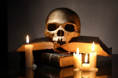 satanism: One human skull on old books near lighting candles on dark background