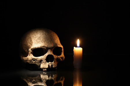 Death concept. One human skull near lighting candle on dark background photo