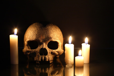 Death concept. One human skull near lighting candles on dark background photo