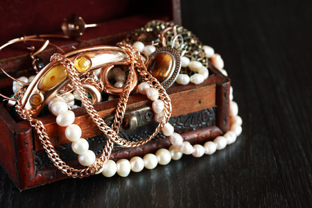 trinket: Nice vintage open box full of various jewelry on dark wooden background