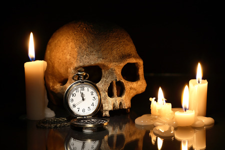 near death: Death concept. One human skull and pocket watch near lighting candles on dark background Stock Photo