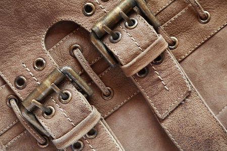 clasps: Brown leather background with belts and clasps