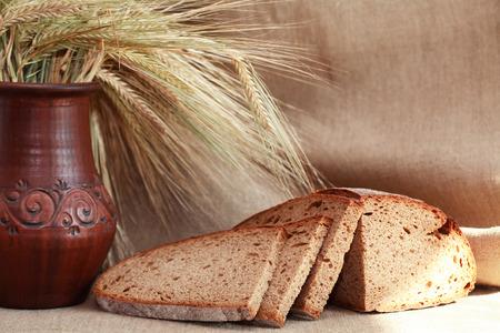 cosiness: Farm still life. Bread near wheat on canvas background Stock Photo