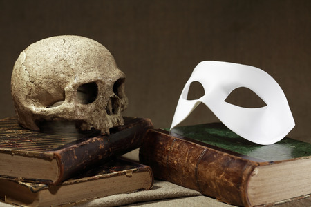 near death: Death concept. Human skull on old book near white mask Stock Photo