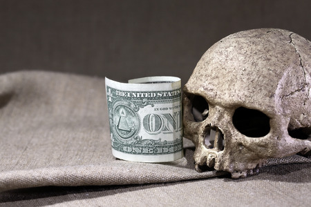 terribly: Bankruptcy concept. Human skull near one dollar bill on canvas background