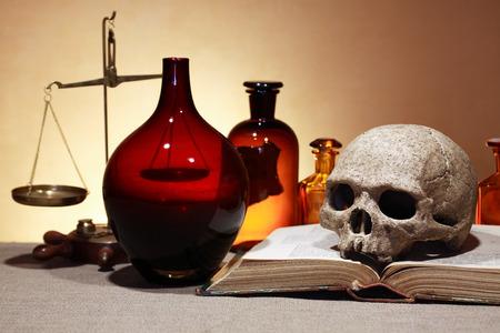 laboratory balance: Cranio umano su vecchi libri vicino scale di peso e antiche boccette di vetro