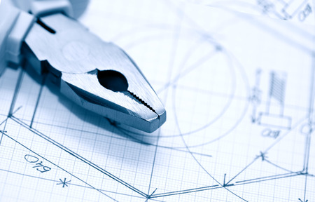combination: Closeup of combination pliers on graph paper with chart Stock Photo