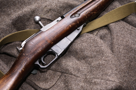 greatcoat: Old famous Russian military rifle on greatcoat background