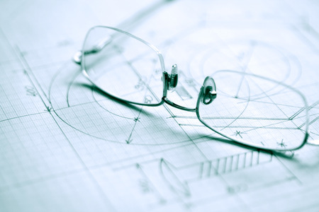 plotting: Closeup of spectacles on graph paper with industrial design