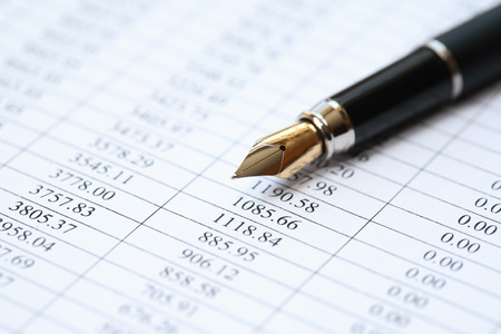 Bookkeeping concept. Closeup of fountain pen on paper background with digits Standard-Bild