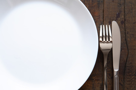 starvation: Closeup of fork and knife near empty white plate