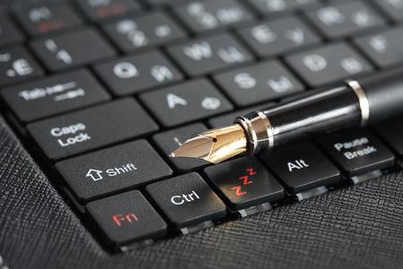Modern literature. Closeup of fountain pen on black computer keyboard