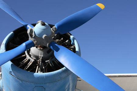 aeroengine: Closeup of old airplane engine with propeller against blue sky