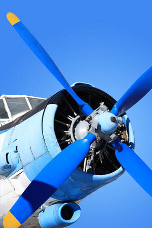 flight mode: Closeup of old airplane engine with propeller against blue sky.  Stock Photo