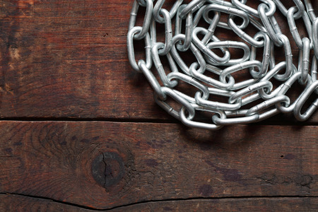 servitude: Metal chain on nice old wooden board Stock Photo