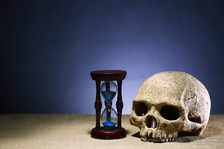 terribly: Death concept. One human skull near hourglass on dark background