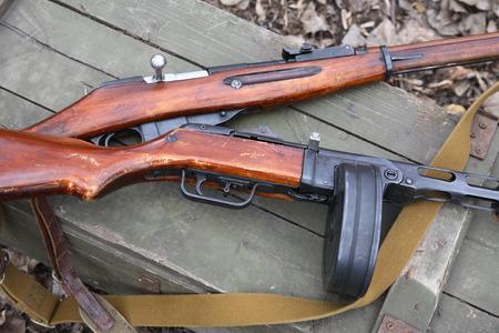 Russian World War II rifle and submachine gun on green wooden box photo