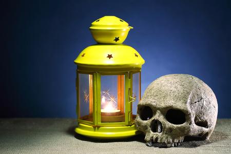 near death: Death concept. One human skull near lighting  lantern on dark background Stock Photo