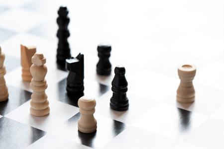 tablero de ajedrez: Blanco y negro pieza de ajedrez situado en el tablero de ajedrez contra la luz