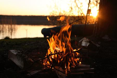 campamento: Camp-fuego sobre la orilla del río una puesta de sol