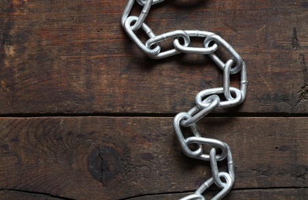 servitude: Metal chain on nice old wooden background Stock Photo