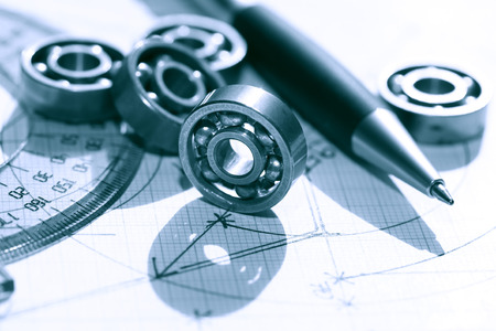 graph paper: Engineering concept. Few ball bearings near ruler and pen on graph paper background