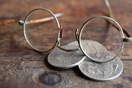 silver coins: Three ancient Russian silver coins near spectacles on wooden background