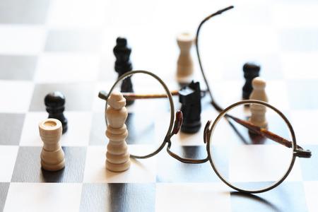 chessman: Black and white chessman set near spectacles on chessboard against light Stock Photo