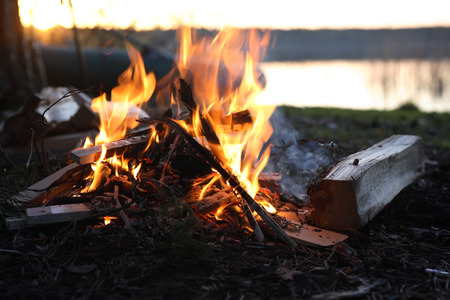 river bank: Summer hiking. Camp-fire on river bank in forest an sunset Stock Photo