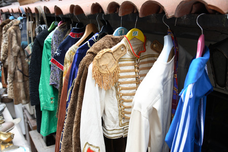 secondhand trade: Curiosity shop. Various vintage clothing hanging on hangers outdoor