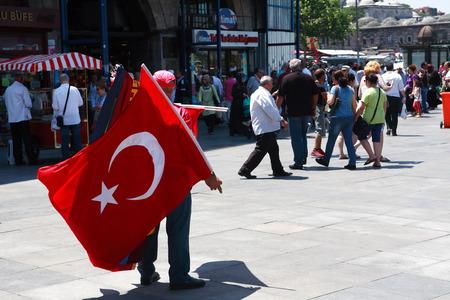 eminonu: Istanbul, Turkey � July 7, 2015: Vendor with Turkish flags for sale on Eminonu square