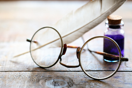 inkpot: Art concept. Closeup of old spectacles near quill and ink-pot on wooden table Stock Photo
