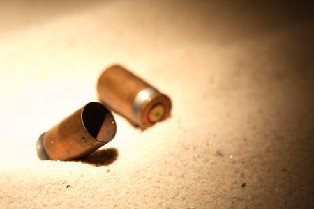 gun shell: Pistol gun shells on sand background with free space Foto de archivo