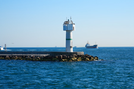 freight traffic: Lighthouse in sea on background with nautical vessel. Bosporus, Istanbul Stock Photo
