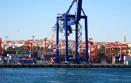 lading: Istanbul, Turkey - July 7, 2015. Panorama with blue sky, sea and container harbour. Closeup of big blue crane Editorial