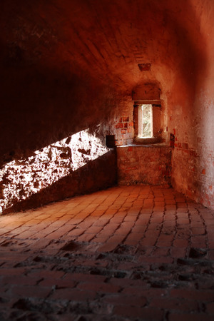 embrasure: Ancient fortress indoors with sunbeam from narrow embrasure