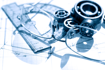 graph paper: Industrial concept. Few ballbearings near ruler and spectacles on graph paper background